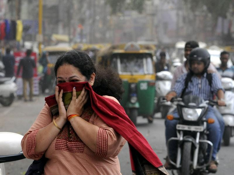A woman covers her face in Indore on Wednesday evening as dusty winds blew across the city. (Arun Mondhe/HT photo)