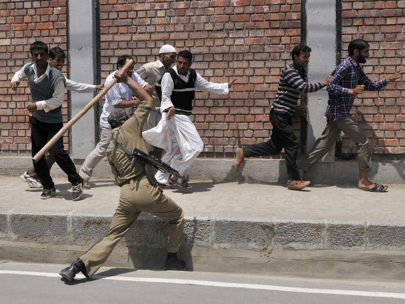 Police beating a Kashmiri daily wage government employee during a protest march in Srinagar. Waseem Andrabi/HT