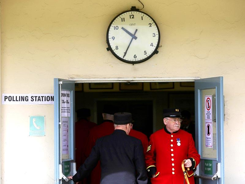 Chelsea Pensioners go in and out of a polling station as they cast their votes in the general election. (Reuters)