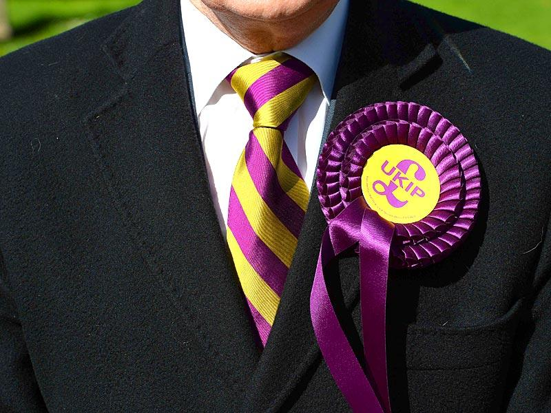 A voter wears a UK Independence Party (UKIP) rosette as he stands outside a polling station in Brighton, southern England. (AFP Photo)