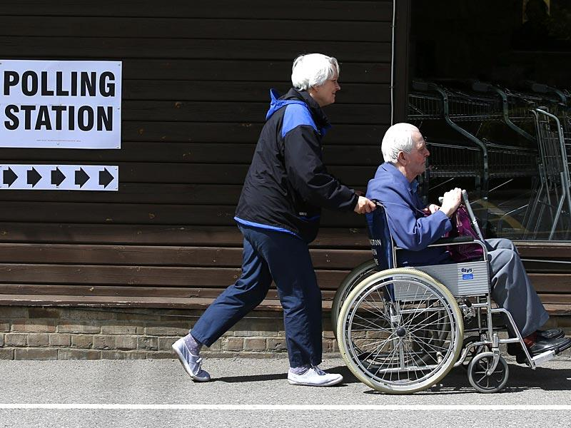 A woman pushes a wheelchair at a garden centre in Chessington, used as a polling station. (AFP Photo)