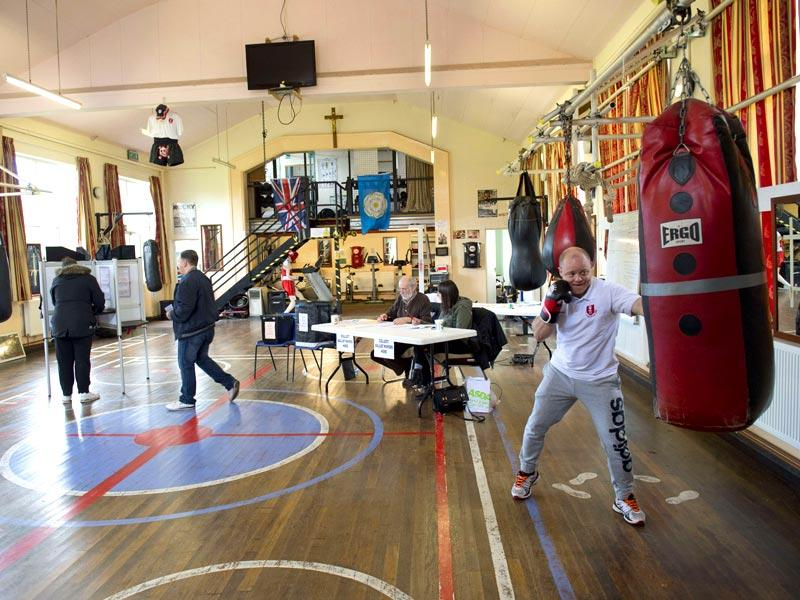 A member (R) boxes as the public vote at East Hull Amateur Boxing Club which is being used as a polling station in Hull, Northern England. (AFP Photo)