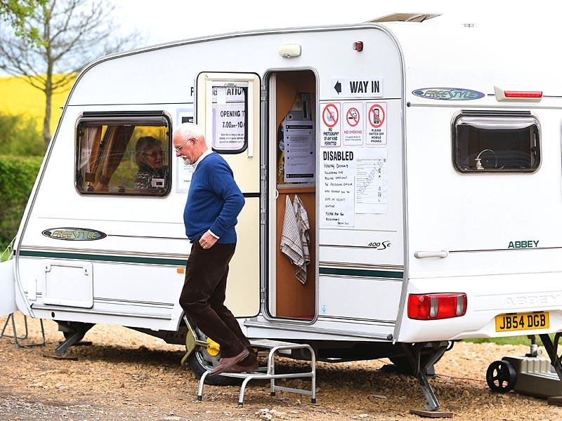 A man leaves after casting his vote in a caravan which is being used as a polling station on Grange Farm in Garthorpe, England. (AP Photo)
