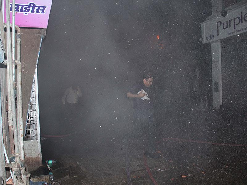 Residents and locals run for safety even as firemen continued to douse fire at a Kalbadevi building, in Mumbai. (Pramod Thakur/HT photo)