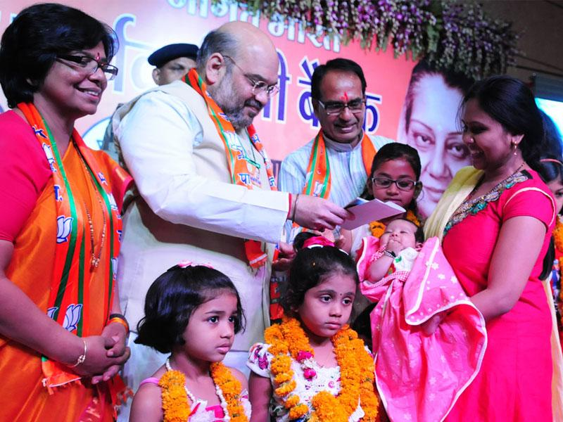 Amit Shah along with CM Shivraj Singh Chouhan hands over certificate of Sukanya Samriddhi Yoajna to a girl child, in Bhopal on Sunday. (Mujeeb Faruqui/HT photo)