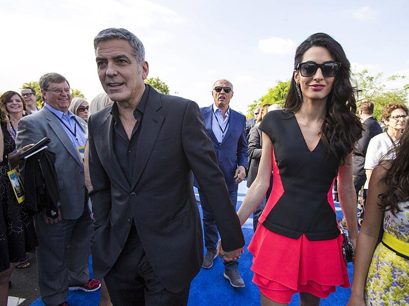 George and Amal Clooney reach hand-in-hand for Tomorrowland premiere. The hand-in-hand pose has become something of a trademark of this power couple. (Reuters)