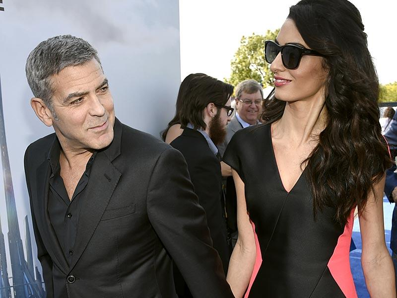 Never too far from each other: George Clooney's lawyer wife Amal wows the world media once again in a frilly pink and black dress. (Reuters photo)