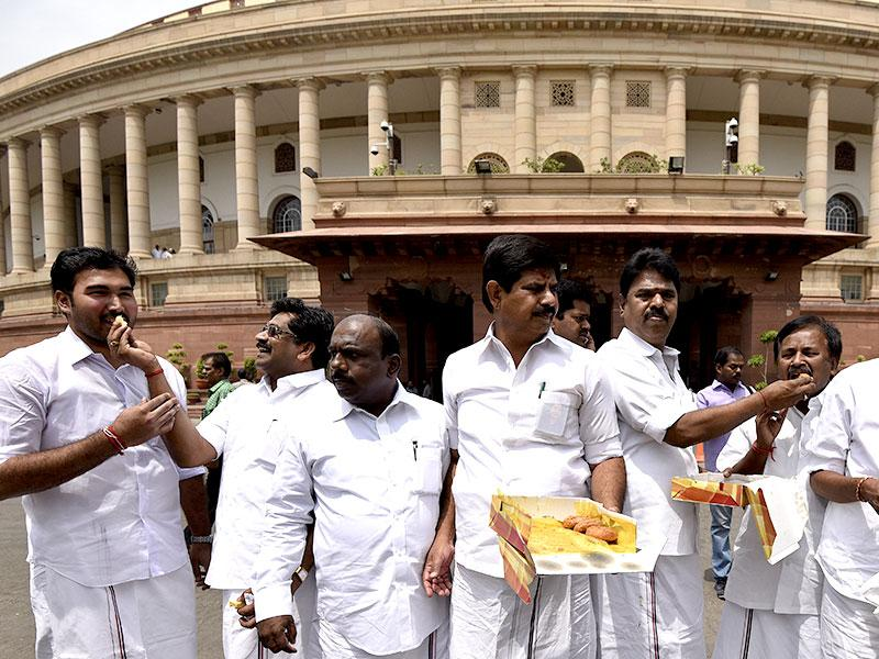 AIADMK MPs celebrate and distribute sweets at Parliament after their leader and former Tamil Nadu Chief Minister J Jayalalithaa was acquitted in the disproportionate assets case by a Karnataka High Court single-bench. (HT Photo/Vipin Kumar)