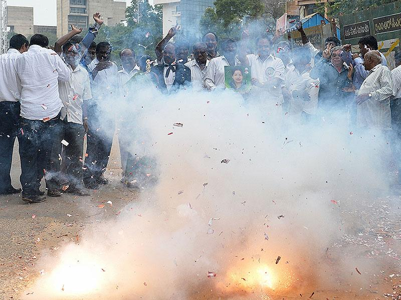 Supporters of All India Anna Dravida Munnetra Kazhagam (AIADMK) supremo, J Jayalalithaa light fire crackers as they celebrate the news of her acquittal in an 18-year-old, disproportionate assets case in Bangalore. (AFP Photo)