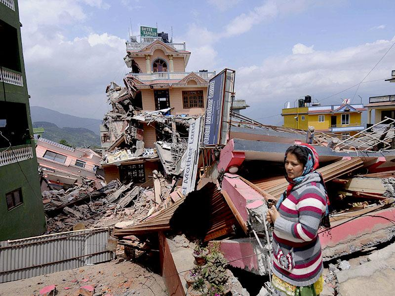 A woman stands amid the debris caused by a fresh earthquake in Nepal. (Burhaan Kinu/ HT Photo)