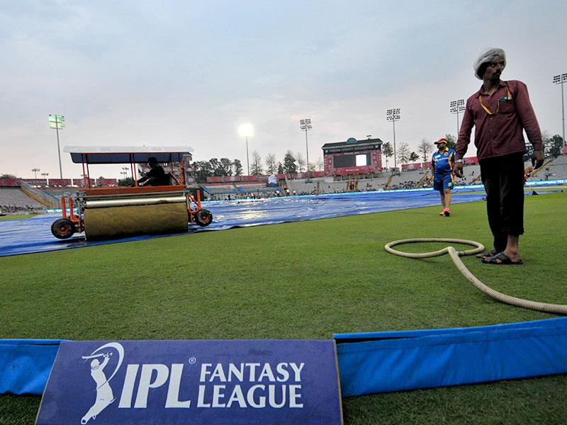 Ground staff work on the field before the rain-hit IPL 2015 match between Kings XI Punjab (KXIP) and Royal Challengers Bangalore (RCB) at Mohali on May 13. (HT Photo)
