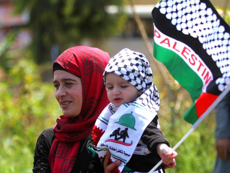 A Palestinian woman who lives in Lebanon carries her child with the Palestinian flag during a protest marking the 'Nakba'. (AP Photo)