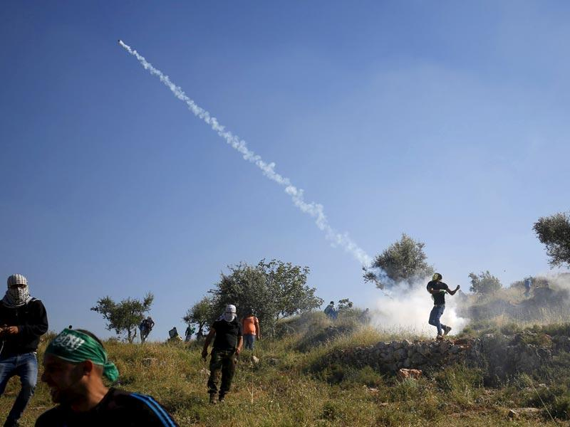 A Palestinian protester throws a tear gas canister fired by Israeli troops during clashes following a rally marking the 'Nakba' near Israel's Ofer Prison near the West Bank city of Ramallah. (Reuters)