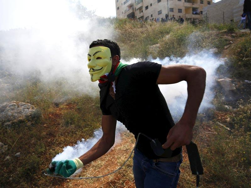 A Palestinian protester with a tear gas canister fired by Israeli troops during clashes following a rally marking the 'Nakba' near Israel's Ofer Prison near the West Bank city of Ramallah. (Reuters)