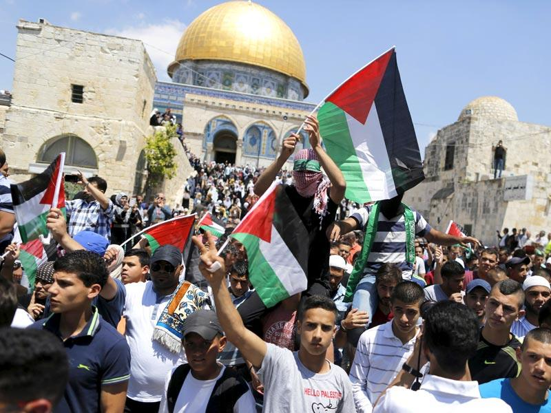 Palestinians wave flags after Friday prayers during a protest to mark Nakba day on May 15, 2015, near the Dome of the Rock on the compound known to Muslims as Noble Sanctuary and to Jews as Temple Mount, in Jerusalem's Old City. (Reuters)