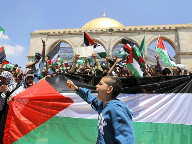 A Palestinian boy shouts slogans as others wave flags after Friday prayers during a protest to mark Nakba day on May 15, 2015 near the Dome of the Rock on the compound known to Muslims as Noble Sanctuary and to Jews as Temple Mount, in Jerusalem's Old City. (Reuters)