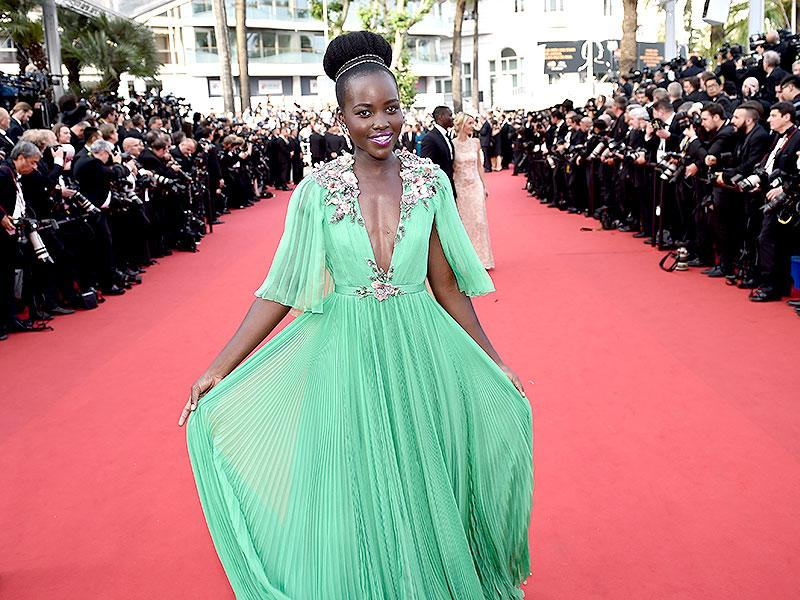Lupita Nyong'o offset her beautiful mint green gown with a vibrant purple lipstick.