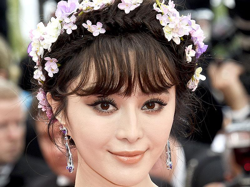 Fan Bingbing teamed an orange-hued lipstick with doe eyes and a whimsical floral headband for a romantic look.