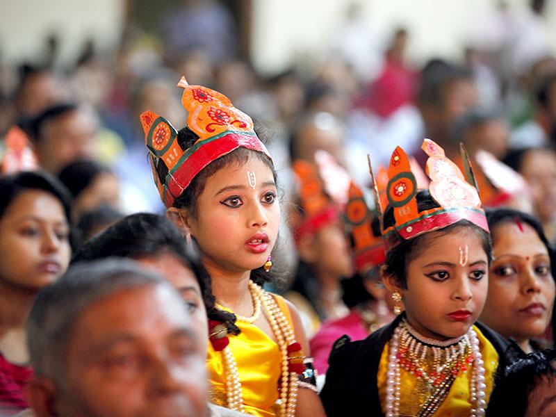 Children dressed in traditional costumes watch a stage performance as they wait for their turn to perform during a cultural festival in Majuli