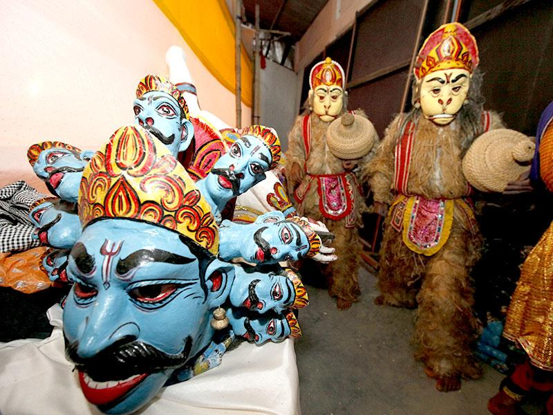 People wearing masks of Hanuman get ready to hit the stage for their bhaona performance