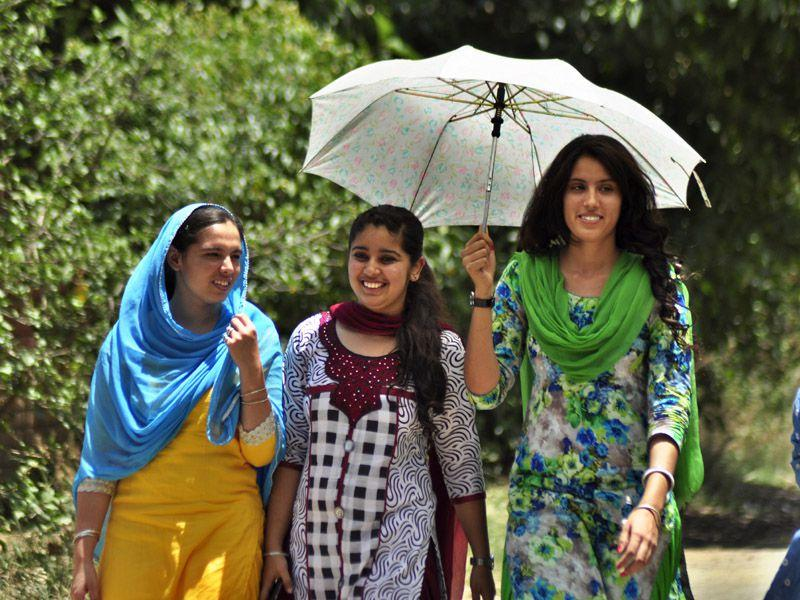 Girls shield themselves with an umbrella to protect themselves from the scorching heat in Ludhiana on Thursday. Sikander Singh Chopra/HT
