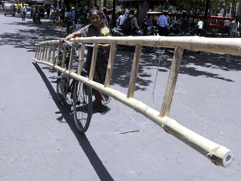 Undeterred by blazing hot weather, a woman carries a ladder on a bicycle in Indore on Thursday. (Arun Mondhe/HT photo)