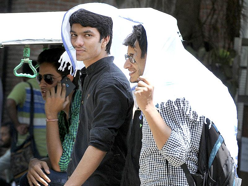 Youth protect themselves from scorching heat in the afternoon on a hot summer day in New Delhi. (HT Photo)