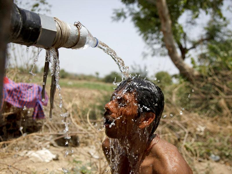 An Indian man takes bath under a tap of a water tanker on a hot day in Ahmedabad. (AP Photo)