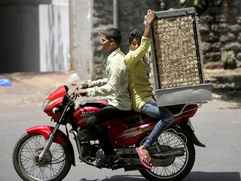 A man carries a cooler on a motorcycle during a hot day in Hyderabad. (AP Photo)