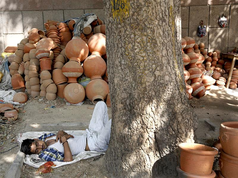 A vendor sleeps near earthen pots in the scorching heat of the Indian Capital. (AP Photo)