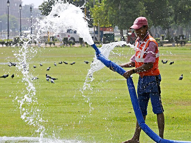 A worker waters a lawn near India Gate in the scorching heat of New Delhi. (HT Photo)