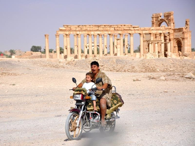 A man rides a motorcycle with a child in the historical city of Palmyra. (Reuters Photo)