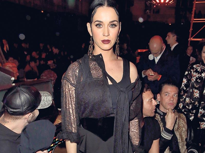 Katy Perry: Wearing a thigh-high slit black sleeveless dress with an asymmetric peplum frill, the singer sat in the front row of the Givenchy Fall/Winter 2015 runway show in Paris, France, in March. The lacy black top, chandelier danglers and gelled hair added a Victorian touch to her Goth look that was complemented with strappy shoes and a black clutch.