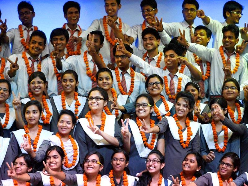 Students celebrate their success at Rani Lakshmi Bai school in Lucknow after the announcement of CBSE Class 12 results. (PTI Photo)