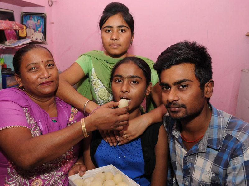 Simran who scored 97.54% with her family members in Kartarpur near Jalandhar. Pardeep Pandit/HT