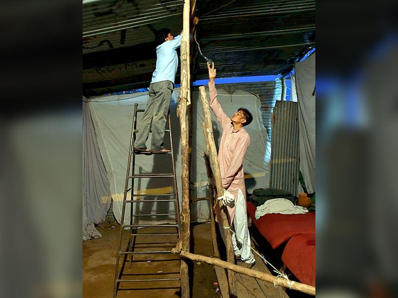 Dharmendra Singh, who at 8ft 1 inch tall claims to be tallest man of India, helps an electrician to fix a bulb inside in an enclosure at Nauchandi Fair in Meerut (AFP Photo)