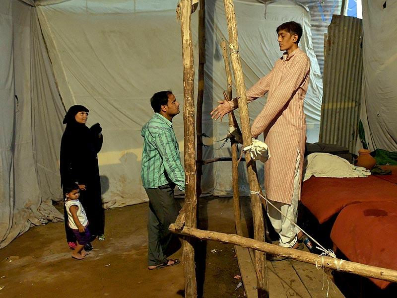 Dharmendra Singh speaks with a visitor as a woman and child look on in an enclosure at the fair (AFP Photo)