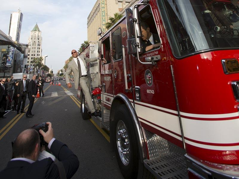 Cast member Dwayne Johnson rides a Los Angeles Fire Department engine, as a LAFD helicopter hovers, as he arrives at the premiere of San Andreas in Hollywood. (Reuters)