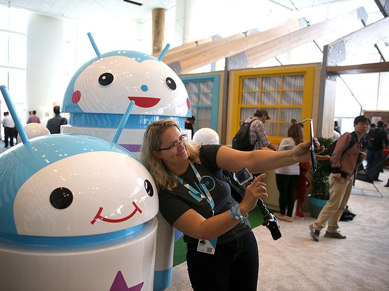 An attendee takes a selfie in front of Android mascots during the 2015 Google I/O conference in San Francisco, California. Photo: AFP / Justin Sullivan