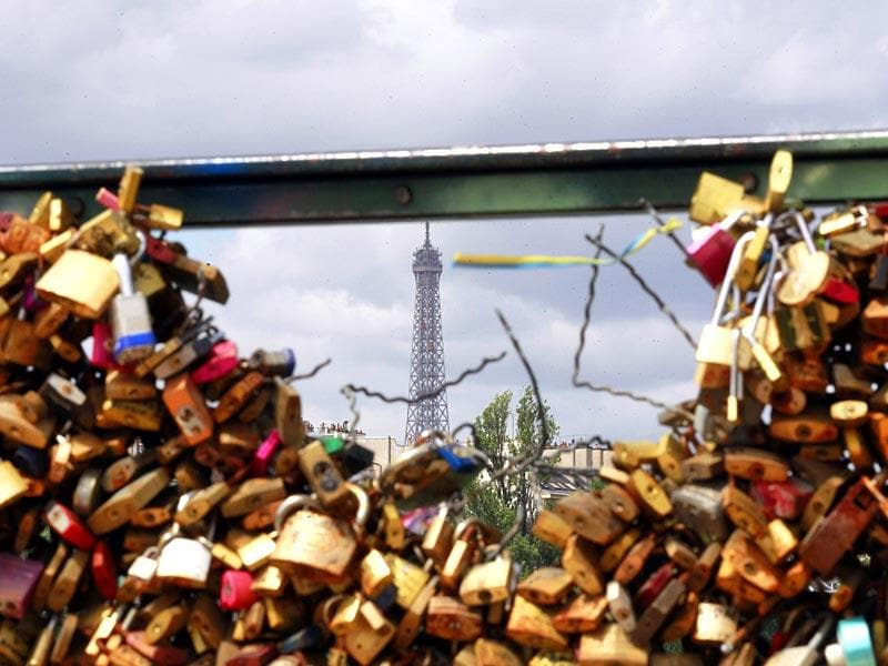The Eiffel tower appears through the partly lock-free railing of the Pont des Arts bridge in Paris. (AP Photo)
