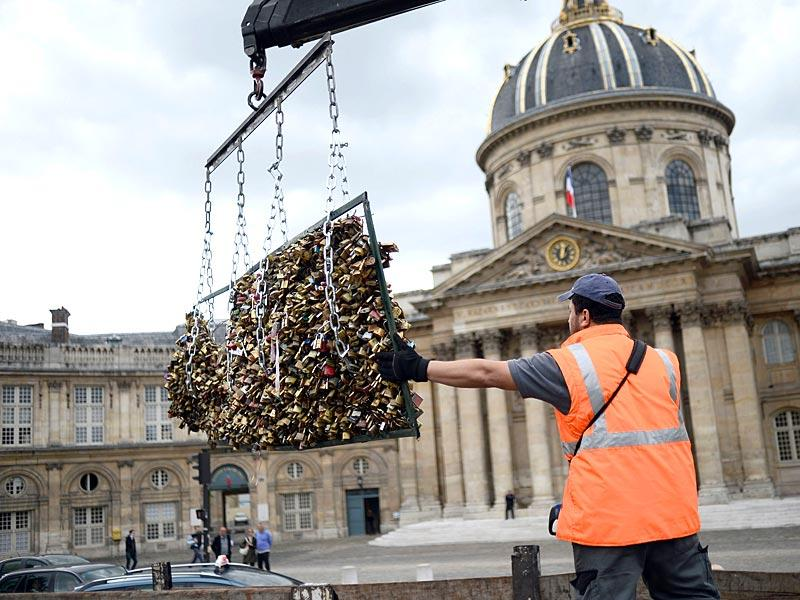 A worker removes 'love padlocks' attached on the railings of the Pont des Arts bridge in Paris. Authorities are looking to recycle the metal used for the padlocks for humanitarian projects 'so that the symbol of love which these couples have invested in them will not be lost entirely'. (AFP Photo)