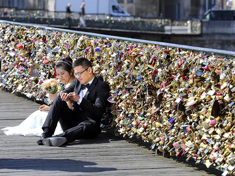 A file photo shows a newly wed couple resting on the Pont des Arts in Paris, France. The pedestrian bridge has become a shrine for amorous tourists and Parisians alike, who seek to immortalise their love by leaving an initialled padlock attached to its metallic grid railings. (AP Photo)