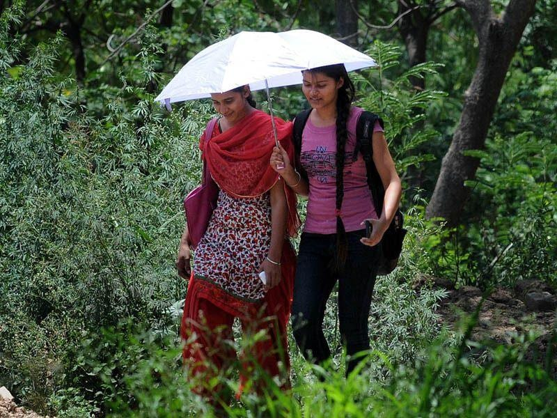 Girls trying to shield herself using umbrella to protect themselves from scorching heat at Sec-42 in Chandigarh. Gurminder Singh/HT