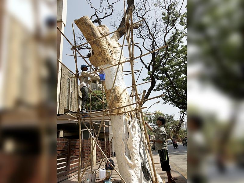 Turning a dead tree into a work of art: A worker paints a dead tree ahead of World Environment Day on June 5 at Matunga, in Mumbai. (Vijayanand Gupta/HT photo)