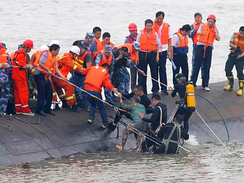 A survivor (green top) is rescued by divers from the Dongfangzhixing vessel which sank in the Yangtze river (AFP Photo)