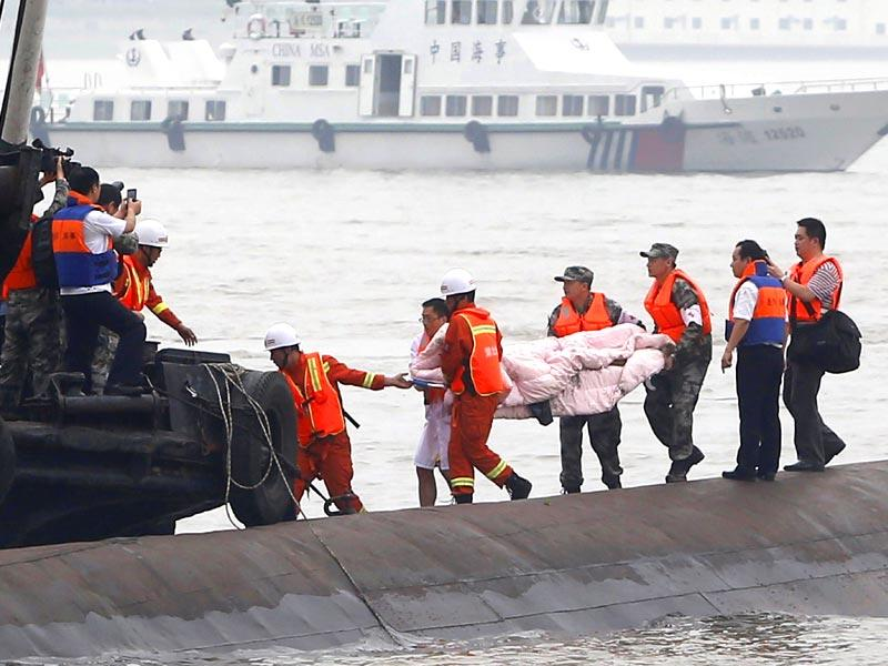 Chinese rescue workers remove the body of a victim from the capsized