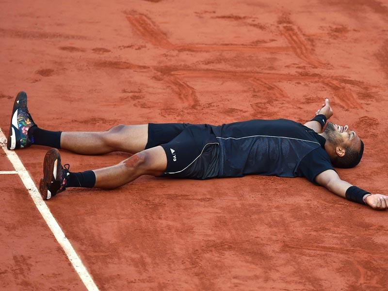 France's Jo-Wilfried Tsonga falls to the ground in celebration after winning his match against Japan's Kei Nishikori during the men's quarter-finals of the 2015 French Open in Paris, France. (AFP Photo)