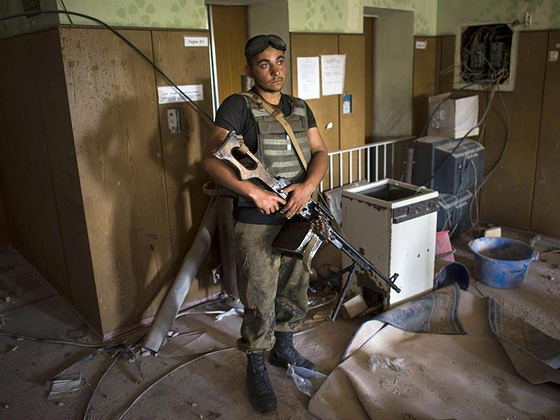 A Ukrainian soldier guards his position near the division line with separatists in Marinka. (AP Photo/Evgeniy Maloletka)