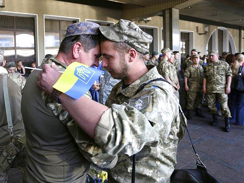 Ukrainian servicemen who came from the region of Donetsk for a rotation embrace each other during a ceremony at the railway station in Kiev. Ukrainian President Poroshenko said on June 5 that Russia had deployed 'an unprecedented' amount of troops on the border with Ukraine as well as claiming there are already thousands of troops in the rebel-held east of the ex-Soviet country. (AFP Photo)