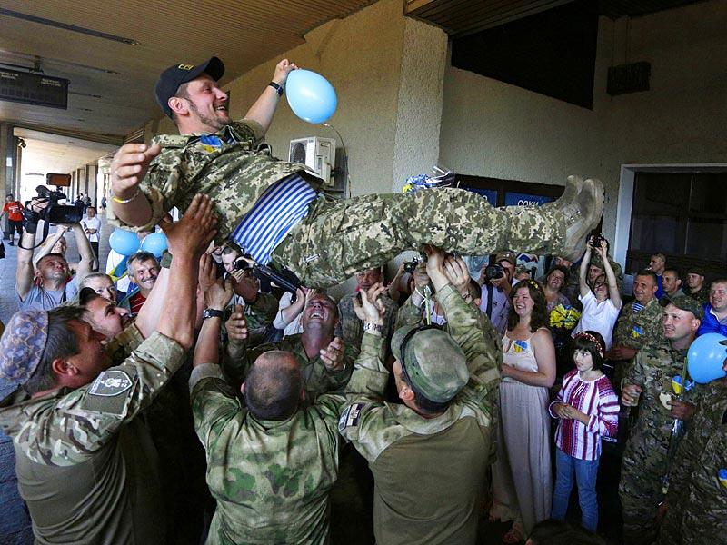A Ukrainian servicemen is held up by his comrades during a meeting ceremony at the railway station in Kiev. (AFP Photo)